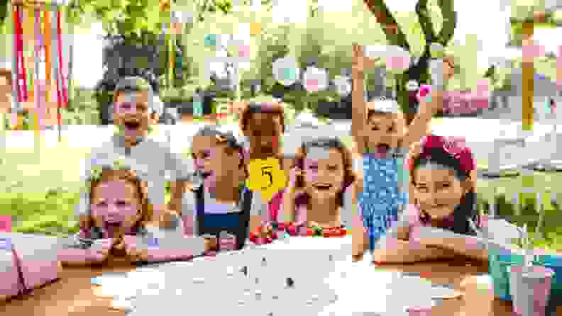 Kids all crowd around for a 5th birthday