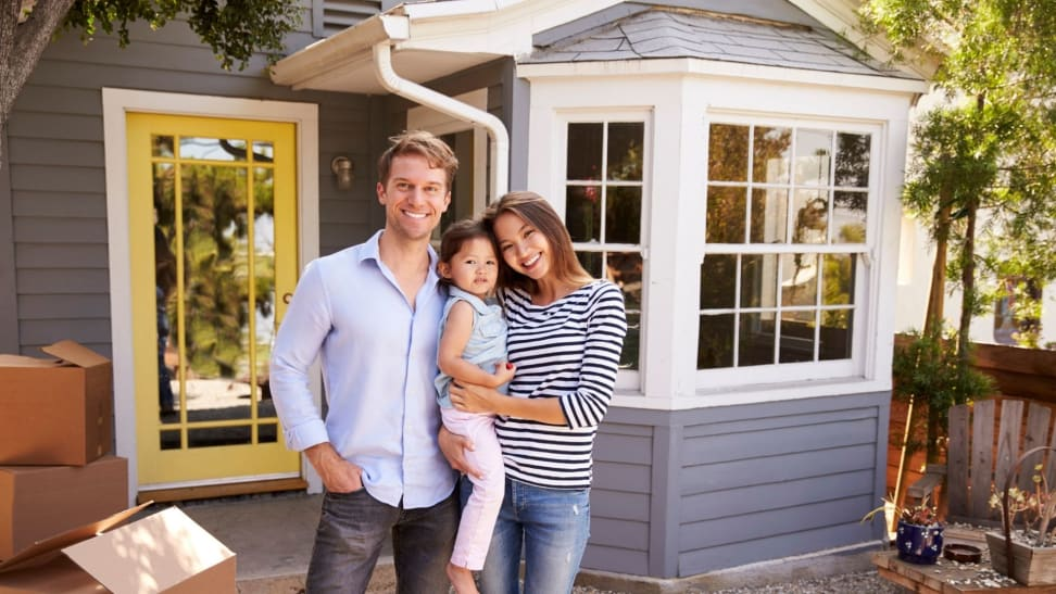 A couple with a small child stand in front of a house with moving boxes