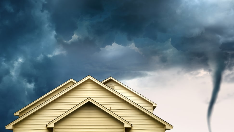 A close-up of the top of a tan-colored home with a tan roof next to an incoming tornado and dark skies