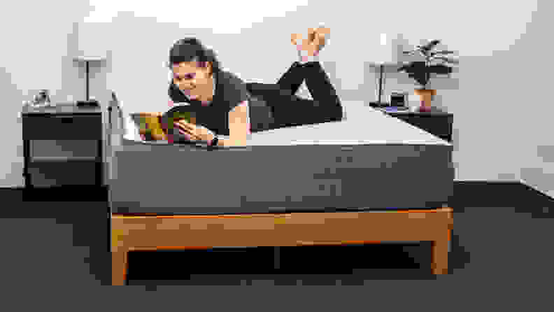 a woman lies on her stomach on the Casper Select and reads
