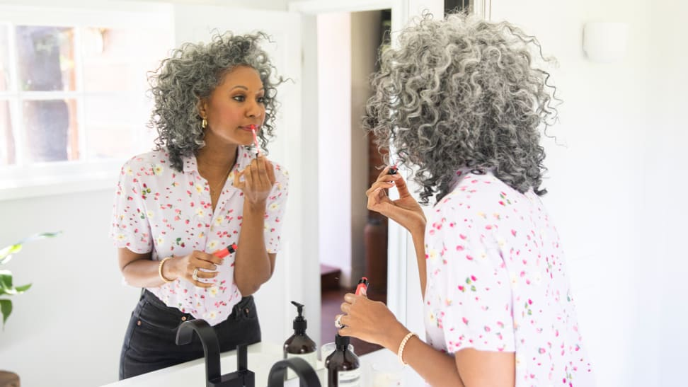 A middle-aged person with dark skin and grey hair looks into a mirror and applies a bright red liquid lipstick to her lips.