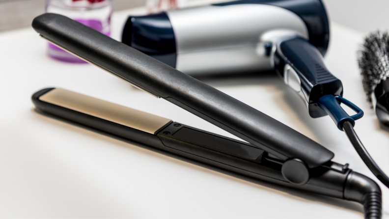 On a sink counter is a black flat iron next to a blow dryer.