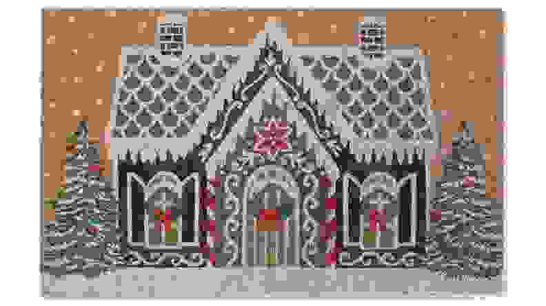 This holiday doormat features a quaint gingerbread house.