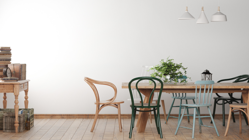 Minimalistic dining room with different styled chairs and wooden dining room table.