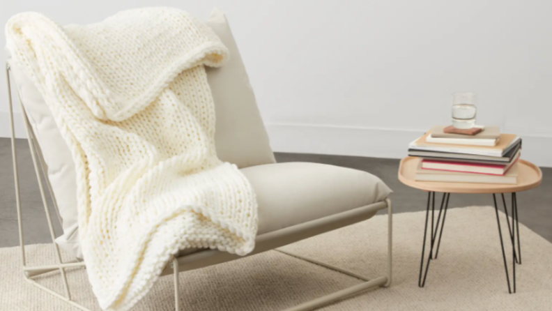 Cream colored blanket draped on tan chair, next to books on small table.
