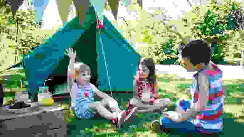 Kids enjoying a party by a small camping-style tent