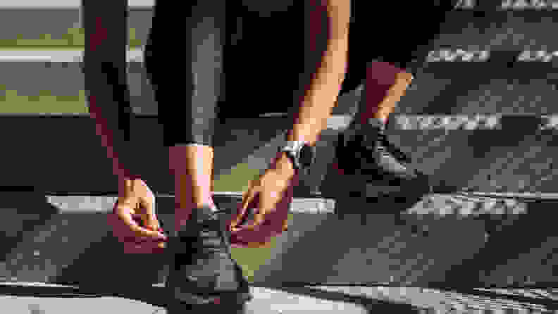 Hands of an anonymous runner tying shoelaces on sneakers.