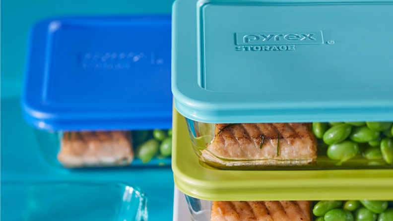An image of several Pyrex storage containers stacked together on top of one another, all with blue or green lids.