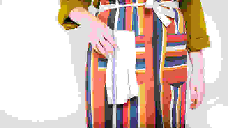 A close-up image of a person wearing an apron their hand in the pocket.