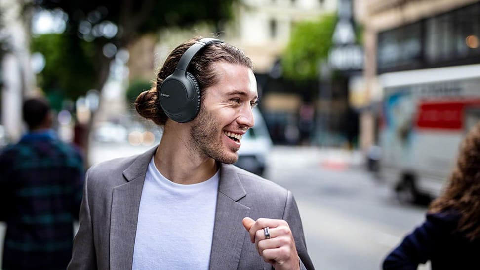 Man smiling while wearing  Sony WH-CH710N noise-canceling headphones outdoors.