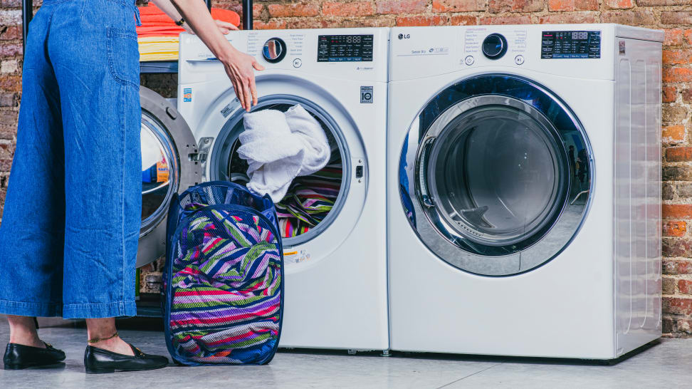 A woman loading laundry into an LG front load washing machine.