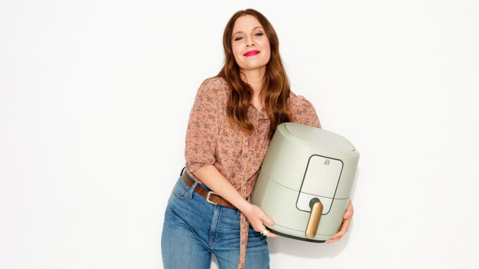 Drew Barrymore holds a sage green air fryer with a golden handle.