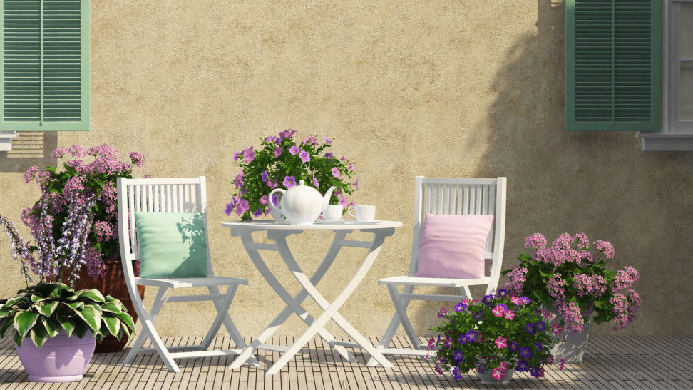 A white bistro set with pink flowers and a tea set.