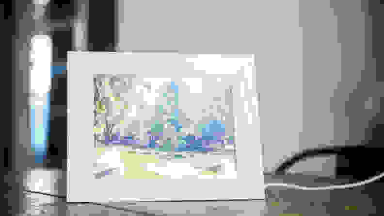 A white Aura digital picture frame displays an image of a brick building surrounded by trees.