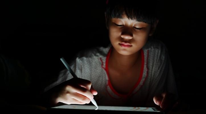 Child using Apple Pencil in the dark