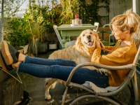 A young adult and their dog enjoys a moment together outside on an apartment balcony.