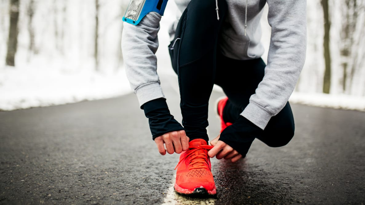 Girl bending down to tie her shoes on a winter run.