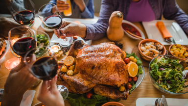 Hands raise red wine glasses over a Thanksgiving dinner table with a roasted turkey.