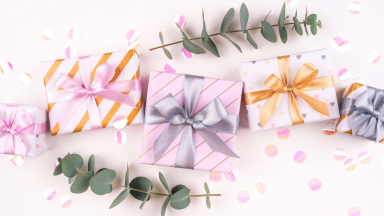 An assortment of colorfully packaged wedding presents surrounded by eucalyptus sprigs.
