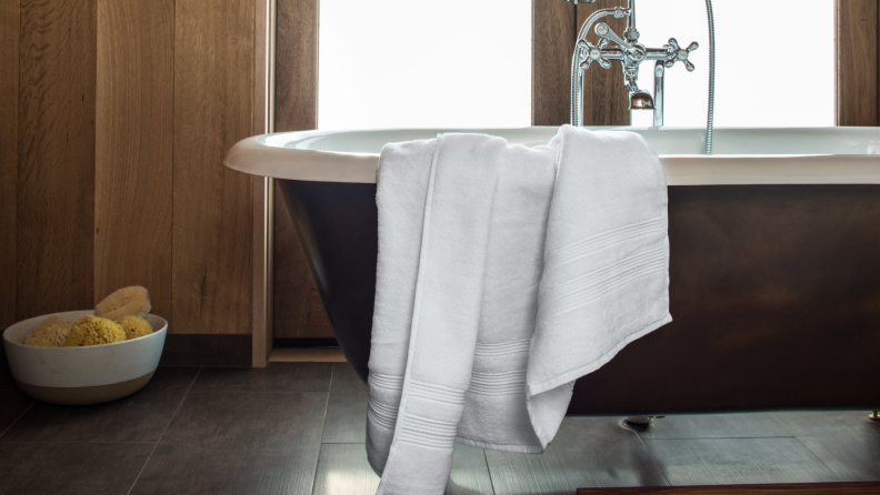 White towel hanging over the edge of brown and white clawfoot tub.