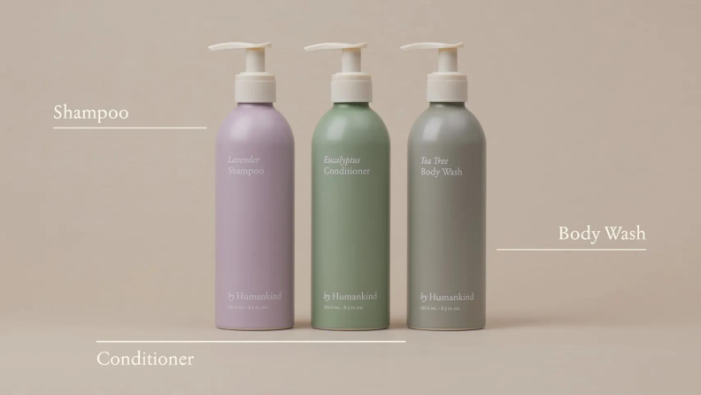 Three bottles containing shampoo in a purple bottle, conditioner in a teal bottle, and body wash in a beige bottle.
