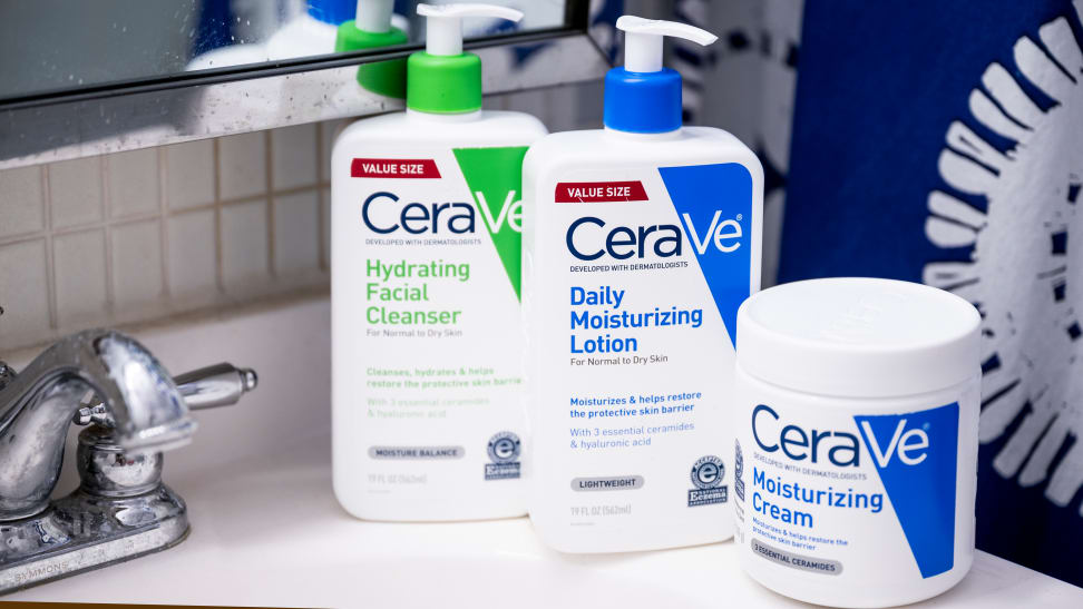 A Cerave cleanser and two moisturizers sit on a bathroom sink.