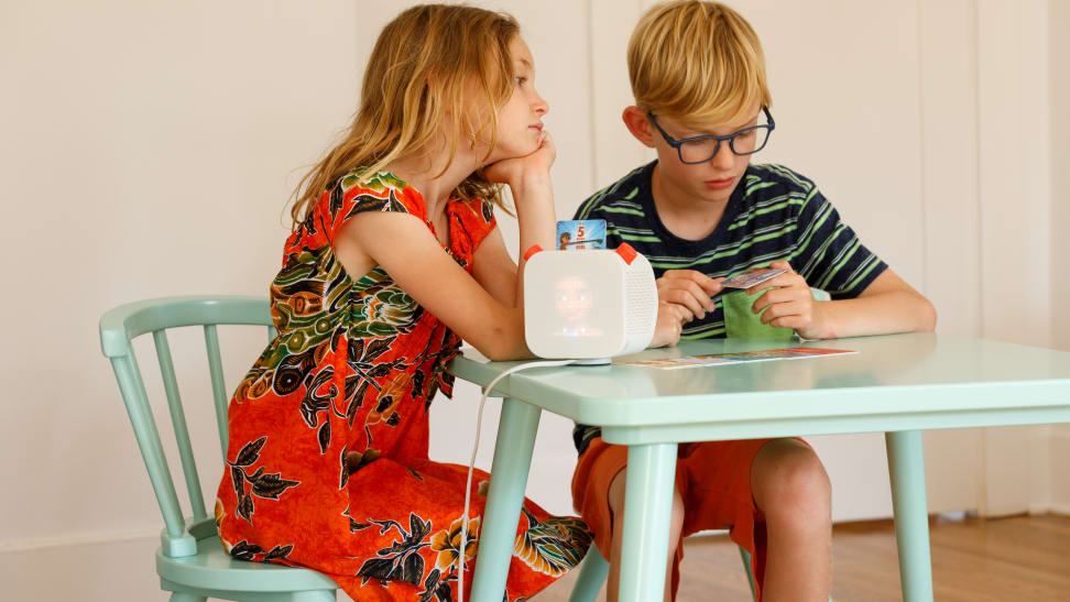 A girl and boy sitting at a table listening to the Yoto Player