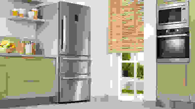 A stainless steel refrigerator unit in a kitchen with light hardwood cabinets, a microwave and an oven.