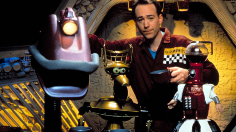 A still from 'Mystery Science Theater 3000' featuring the host and several robots.