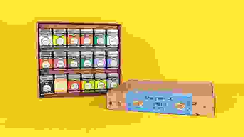An assortment of spice tins arranged in a cardboard box against a bright yellow background.