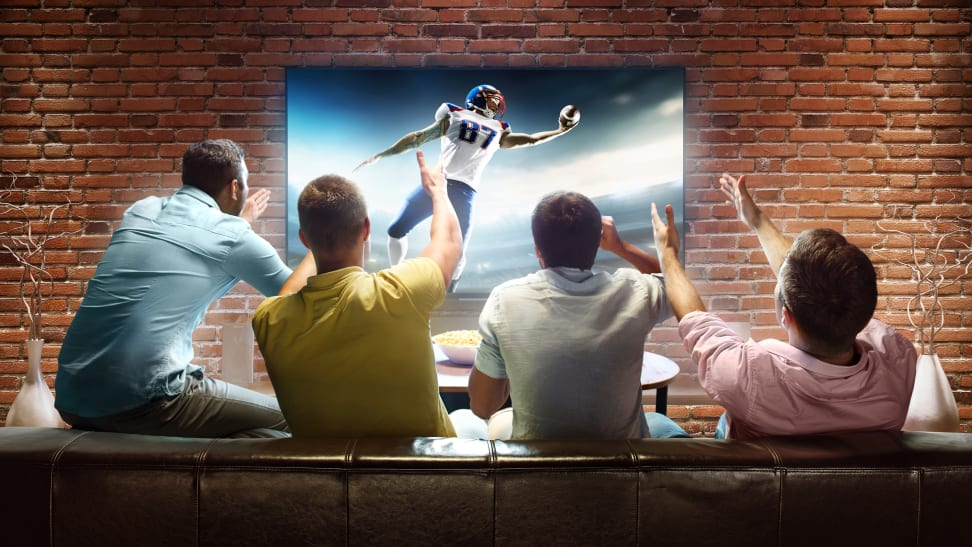 A group of friends celebrating the home team scoring a touchdown in a televised football match