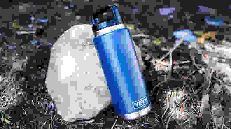 A blue Yeti Rambler water bottle leaning against a rock on the ground.