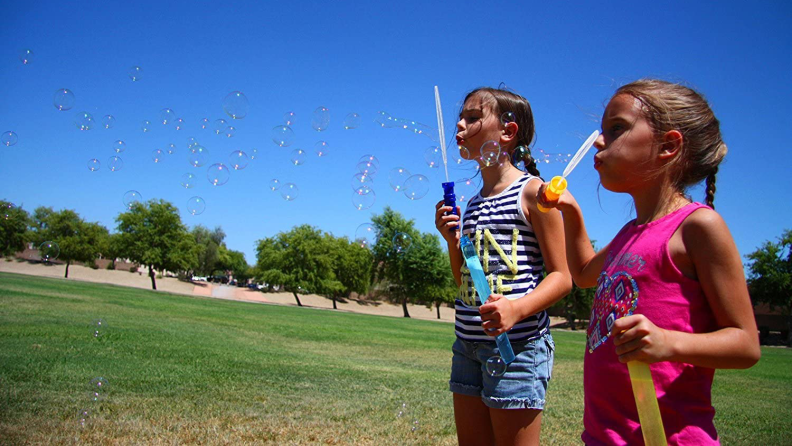 Two girls blowing bubbles with bubble wands