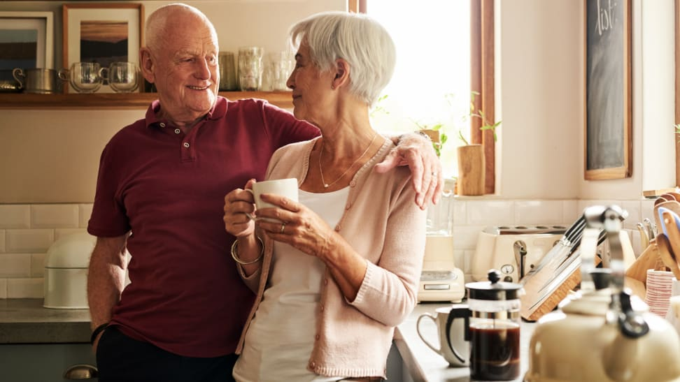 A senior couple spends quality time in their kitchen together.