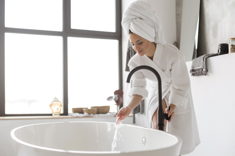 Woman in bathroom wearing robe and towel wrapped around her hair while standing over running water in bath tub