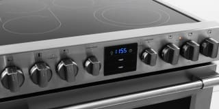 A close-up photo of an electric range highlighting the electric cooktop and the oven control knobs.