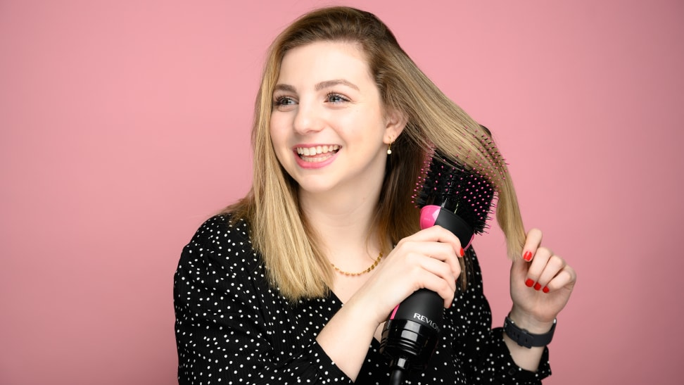 A woman using the Revlon One-Step Hair Dryer and Volumizer.