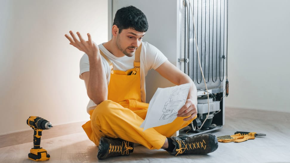 A man sits on the ground near a fridge, near a drill and some manuals. He's reading the fridge's warranty and putting up one hand in confusion at what he's reading.