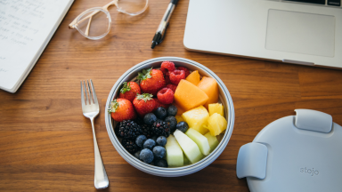 In the center of the desk, there's a Stojo bowl full of strawberries, blueberries, blackberries, cut orange, and other fruits. Beside the bowl, there's a fork. There's a notebook, a pair of glasses, a marker, and a MacBook scattered.