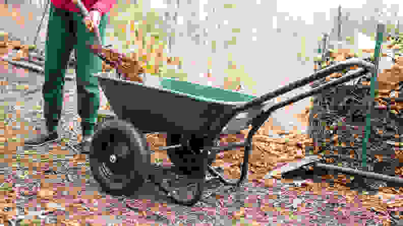 A person uses a shovel to fill the Marathon Green Yard Rover with dirt.
