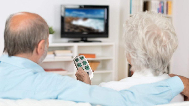 A senior couple navigate TV channels with a universal remote.