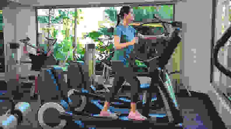 A woman using an elliptical machine at the gym.