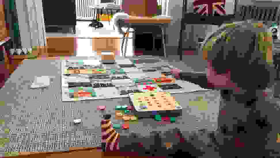 A toddler plays with Cubetto in the living room