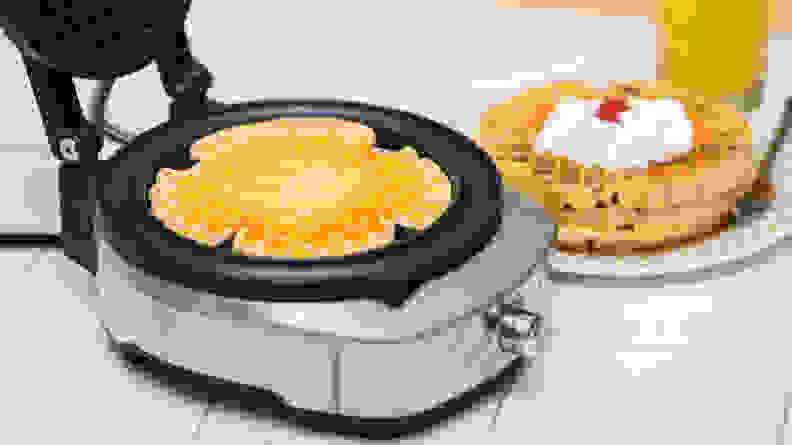 An open Breville BREBWM520XL maker with a cooked waffle and a plate of waffles in the background.