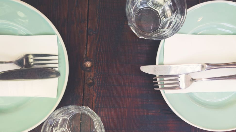 Dinner place setting for two diners on a wood table.