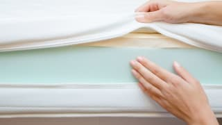 hands show the layers of a mattress