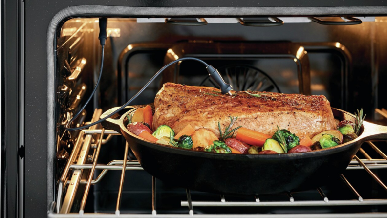 A pot of roasted pork with vegetables is in an oven. A meat thermometer is probed into the meat.