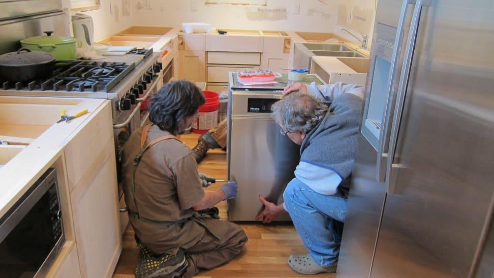Men installing a dishwasher