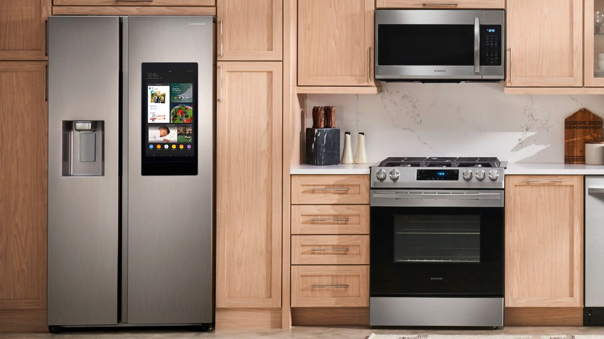 The Samsung RS27T5561SR Side-by-Side Refrigerator in a modern kitchen, alongside other Samsung kitchen appliances.