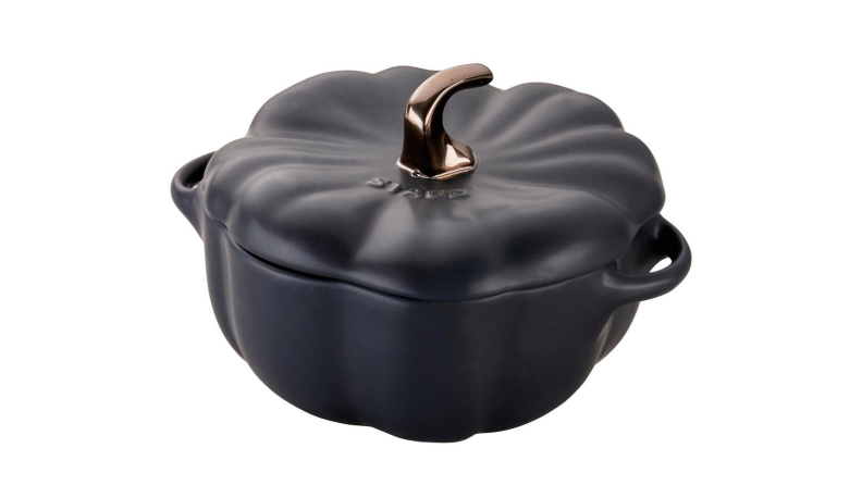An image of a Staub Dutch oven in the shape of a pumpkin, with matte black and bronze accents